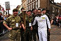 An Olympic torchbearer, right foreground, holds the torch amid members of the Guard of Honour May 24, 2012, in Gloucester, England 120524-O-ZZ999-003.jpg