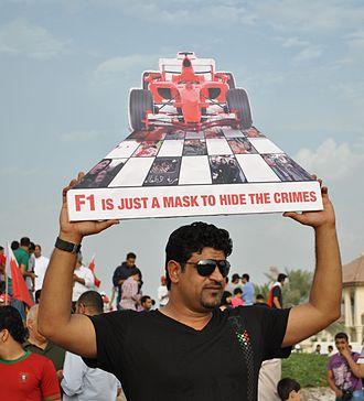 2013 Bahrain Grand Prix - A Bahraini protester holding an anti-F1 sign