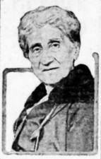A black and white photograph of the head and shoulders of a woman