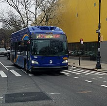A front view of a curved mostly blue bus passing a bright yellow building
