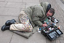 Man lying on pavement, painting chewing gum