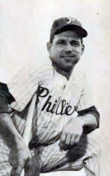 "A smiling man wearing a pinstriped baseball uniform with ""Phillies"" across the chest and a dark baseball cap with a white ""P"" on the face leaning on a baseball bat"