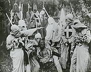 """Encapuchados del Ku Klux Klan agarran a Gus, un negro que el cineasta, de manera estereotipada, describe como """"un renegado, un producto  de las doctrinas inmorales respaldadas por los republicanos."""""""