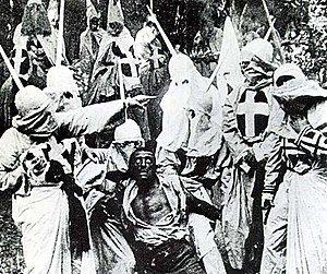The Birth of a Nation - Hooded Klansmen catch Gus. Gus was portrayed in blackface by white actor Walter Long.