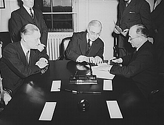 Jean Monnet - French conclude agreement on lend-lease and reverse lend-lease. Jean Monnet, representative of the French Provisional Government signs agreements. Left to right: Henri Bonnet, French Ambassador, Joseph C. Grew, Undersecretary of State and Jean Monnet.