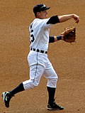 Baseball player in white uniform in a baseball throw followthrough position.  His arm is forward with his hand down and his left hand is gloved. His left foot is planted and his right foot is in the air behind him.