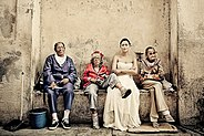Bride sitting on a bench with Cubans