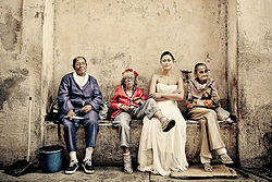 Bride sitting on a bench with Cubans.jpg