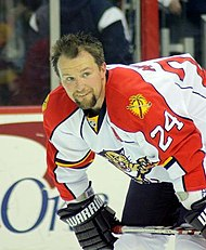 Bryan McCabe in a red and white Florida Panthers jersey, bending forward and looking to the right