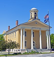 A pale-yellow two-story building, seen from the side, with a classically-styled colonnade on the front underneath a small domed cupola