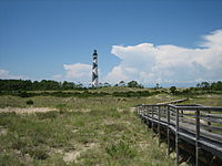 Walkway over dunes leading to a lighthouse