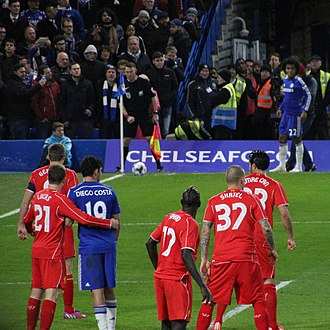 Corner kick - Liverpool (red) players prepare to defend a Chelsea (blue) corner.