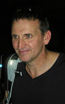 An upper-body shot of a middle-aged Eccleston with short dark hair, wearing a dark top, with the white strap of a bag slung over his right shoulder.