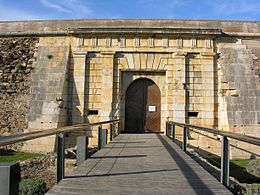 Photo shows the arched gate of a stone fortress and the bridge that approaches it.