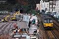 Dawlish - GWR 143612+150219 passing the sea wall works.JPG