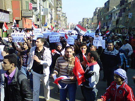 Egypt, 25 January 2011: marchers in Cairo with 'OUT' signs on the 'Day of Anger' against President Mubarak. On 11 February he left office. Day of Anger marchers with out signs.jpg