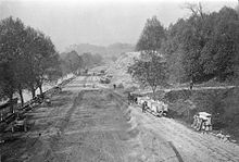 A wide dirt road beside a tree-lined river with several carriages and some vehicles