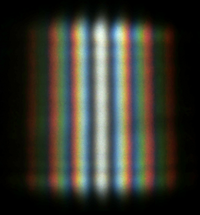 A double-slit interference of the sunlight passing through two slits ~1 cm long and ~0.5 mm apart. At the top and the bottom of the image the interference on the edge of the slit produces noticeable variation of the brightness.