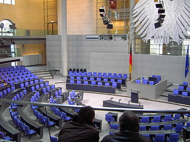 The cabinet bench in the Reichstag building (to the left of the flag) with the raised seat of the chancellor in the front row Dt Bundestag Plenarsaal 2006.jpg