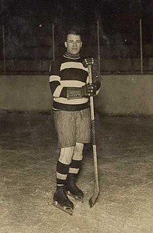 Gerard wearing skates and holding a hockey stick poses for a photo.