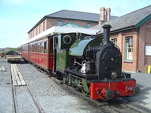A green saddle-tank engine stands in front of a large brick station building. Behind the engine are four red coaches.