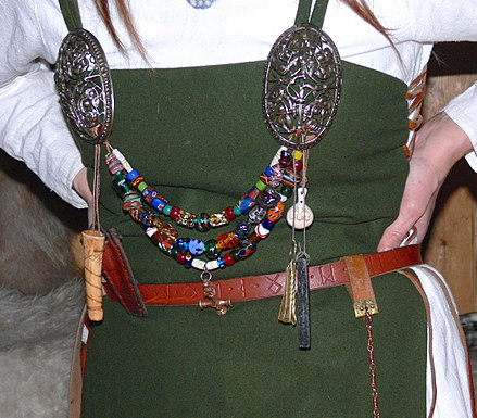 Typical jewellery worn by women of the Karls and Jarls: ornamented silver brooches, coloured glass-beads and amulets Eiriksstadir - Wikingerschmuck.jpg