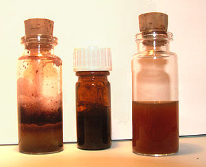 Iron gall ink - Homemade ink. On left, a solution of iron (from nails) and vinegar. On right, oak extraction. The two are mixed immediately prior to use to produce the ink, centre.
