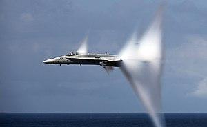 F-A-18C Hornet in transonic flight, with condensation cones.jpg