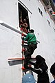 Flickr - Official U.S. Navy Imagery - Sailor climbs aboard Carnival cruise ship from rigid hull boat..jpg