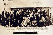 Large group of men, with Arabic caption