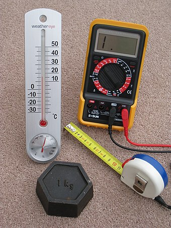 Four domestic quality contemporary measuring devices that have metric calibrations - a tape measure calibrated in centimetres, a thermometer calibrated in degrees Celsius, a kilogram weight (mass) and an electrical multimeter which measures volts, amps and ohms FourMetricInstruments.JPG