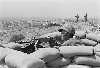 U.S. Marine sits in a foxhole and points a mac...