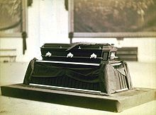 A casket sits on a bier in this black-and-white photo