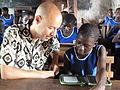 Ghana student reading with Worldreader CoFounder David Risher.jpg