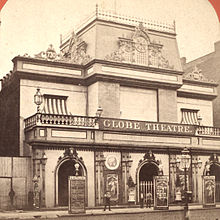Photograph of the building in a different alteration, with a few people in front watching the photo being taken