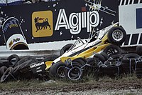 A badly damaged yellow-and-white racing car after impact into a tyre wall