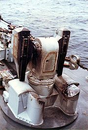 An empty missile launcher on the front of a warship, it has scorch marks on it. In the background there are empty shell casings.