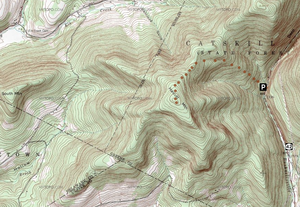 "A topographic map with green and white background behind brown contour lines with a semicircle of brown dots in the middle beginning at a black and white ""P"" sign on the right. Below it is a sign with the number 42."