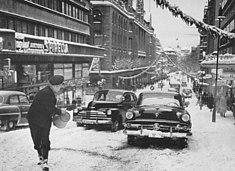 "Hamngatan mod øst ved ""Hamngatsbacken"" et vinterdag 1955 og samme sted en vinterdag 2010, ""Hamngatsbacken"" blev gravet bort 1967-1968.   Til venstre ses Hesteskopaladset og NK, den eneste bebyggelse i den forhenværende kasse som overlevede Norrmalm-reguleringen."