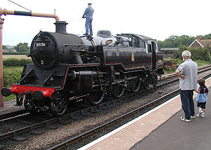 Heritage railway - Scene on a heritage railway: A tank engine takes on water through a water crane at Bishops Lydeard station on the West Somerset Railway, Somerset, England