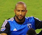 A man with a shaven head wearing a blue soccer jersey.