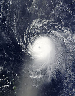 Satellite image of a slightly elongated tropical cyclone over blue waters; an eye, visible as a void at the center of the mass of white clouds is visible. Small green islands dot the lower-left corner of the image.