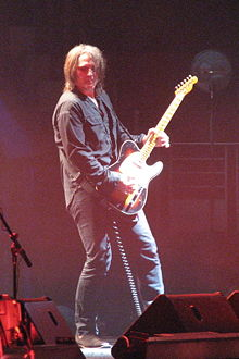 Haug is playing his guitar, while leaning forward and to his right. His hair is shoulder-length, he wears a dark shirt and dark pants. Some band and stage equipment is near his feet.