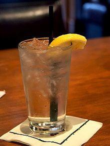 A clear glass filled with water, ice cubes, a slice of lemon, and a straw