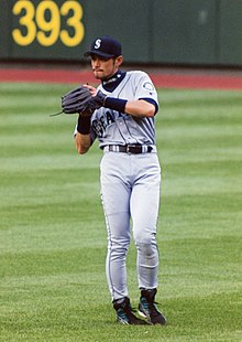 e0ec904f65a A Japanese man wearing a grey Seattle baseball uniform fielding a ball in  the outfield.