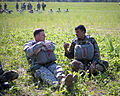 Indian and U.S. Army paratroopers chat while waiting for CH47 Chinook helicopters to pick them up for an airborne operation in 2013.jpg