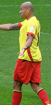 A man with bald hair who is wearing a yellow top, red shorts and red socks.