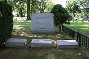 """Three Robinson family gravestones are placed next to a larger family headstone with the quotation """"A life is not important except in the impact it has on other lives"""", inscribed with Robinson's signature"""