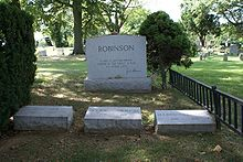 "Three Robinson family gravestones are placed next to a larger family headstone with the quotation ""A life is not important except in the impact it has on other lives,"" inscribed with Robinson's signature"