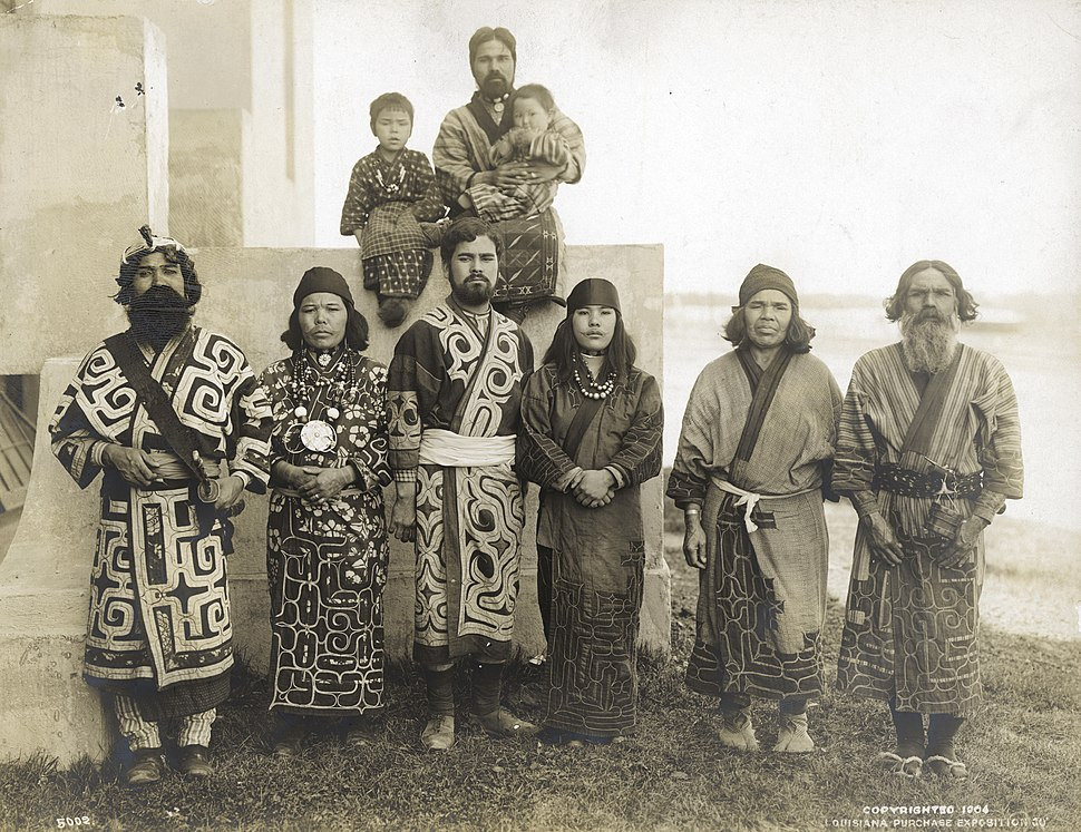 Japanese Ainu group of four men and two women (standing) with seated young boy and man holding a baby in the Department of Anthropology exhibit at the 1904 World%27s Fair